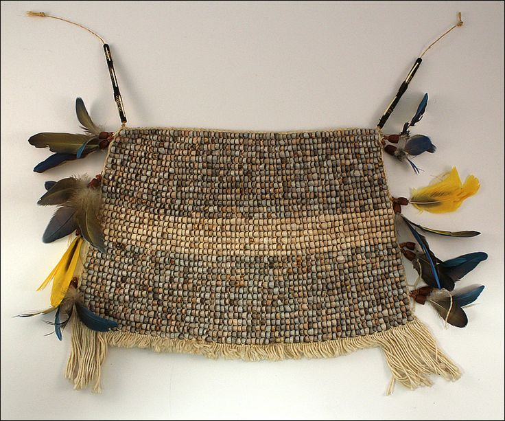 Loin Cloth, Waiwai, Guyana, Brazil, South America. Loin Cloths are made of tiny tururri seeds painstakingly strung and woven together to produce a beautifully textured garment. It is worn around the waist, ties in the back and is trimmed with feather danglers.  Materials: macaw feathers, porcupine quills, tururri seeds, nuts, cotton. Period: circa 1970.