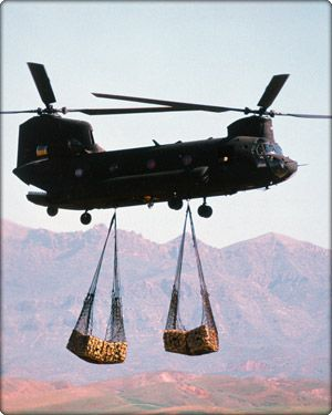"""The Chinook is a multi-mission, heavy-lift transport helicopter. Its primary mission is to move troops, artillery, ammunition, fuel, water, barrier materials, supplies and equipment on the battlefield. Its secondary missions include medical evacuation, disaster relief, search and rescue, aircraft recovery, fire fighting, parachute drops, heavy construction and civil development."" Chinook in flight carrying cargo (Neg#: DVD-1100-2)"