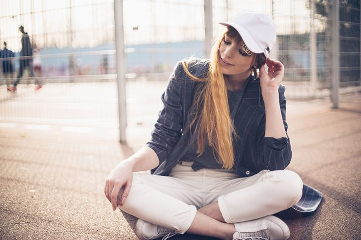 Sporty Pinstripe street style with pinstripe coat and white cap with piercing rings, sporty Berlin street style fashion photography