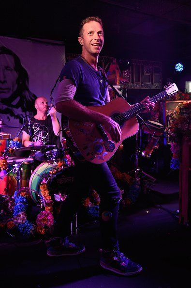 Frontman Chris Martin of Coldplay in concert with his band. Background: Coldplay drummer and composer Will Champion.