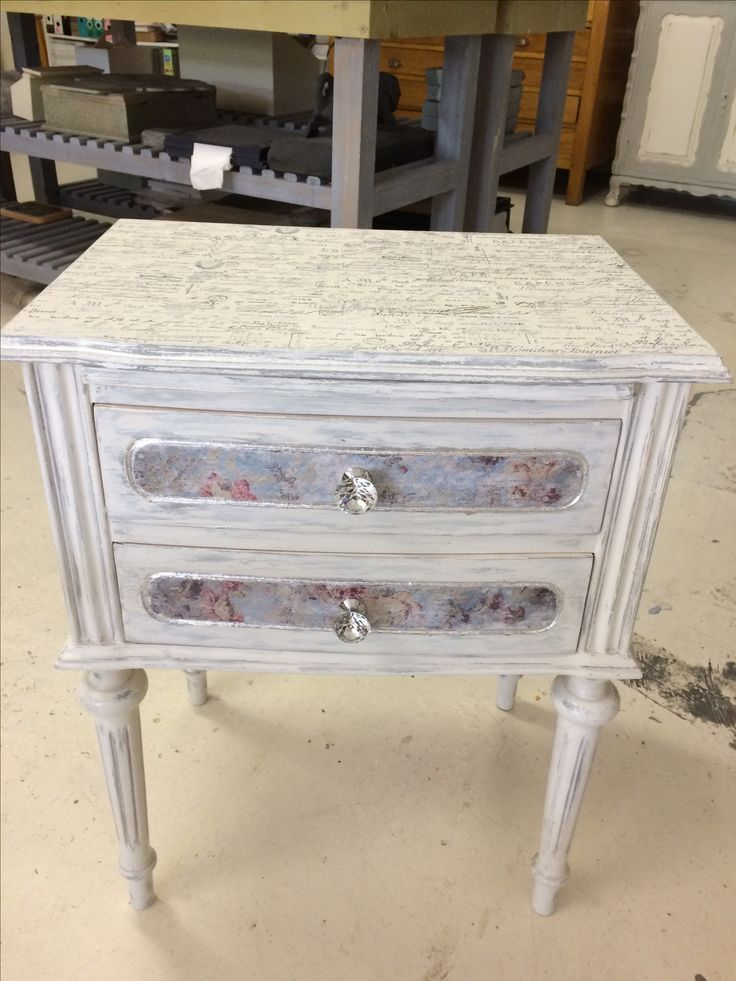 """Sheryl worked very hard on this iconic little bedside table with fluted legs. Annie Sloan Chalk Paints in Paris Grey and Old White were dry-brushed onto the wood. Transferred images were """"podged"""" over the paint technique, then sanded back to create the whimsical gentle colored inset drawer panels. Silverleafing was added for extra detail and genuine crystal handles replaced the old iron ones adding a touch of glamour and sparkle!"""