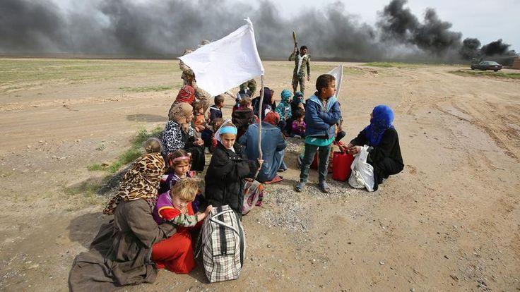 DRAPEAU BLANC.Ce petit groupe de femmes et d'enfants irakiens patiente sous la fragile protection de deux drapeaux blancs et de trois soldats des forces gouvernementales aux portes de Samarra, un trésor architectural de l'ancienne Mésopotamie attaqué le 28 février par les djihadistes de Daech, puis victime d'une contre-offensive massive menée par l'armée régulière et les milices chiites, soutenues par les aviations irakienne et américaine. Autant dire que ce fragment de désert, hautement…