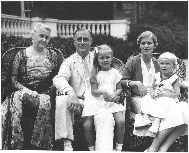 """FDR - seated in front of his home """"Springwood"""" at Hyde Park, New York l-r: Sara, FDR with Sistie, Anna Roosevelt Halsted and Buzzie. 7/17/1932"""