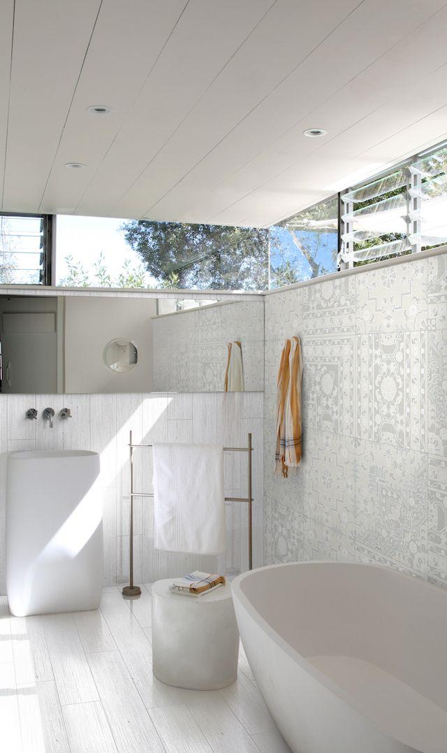 White timber-look floor tiles in bathroom; freestanding bath, pedestal basin and towel rack; high louvre windows