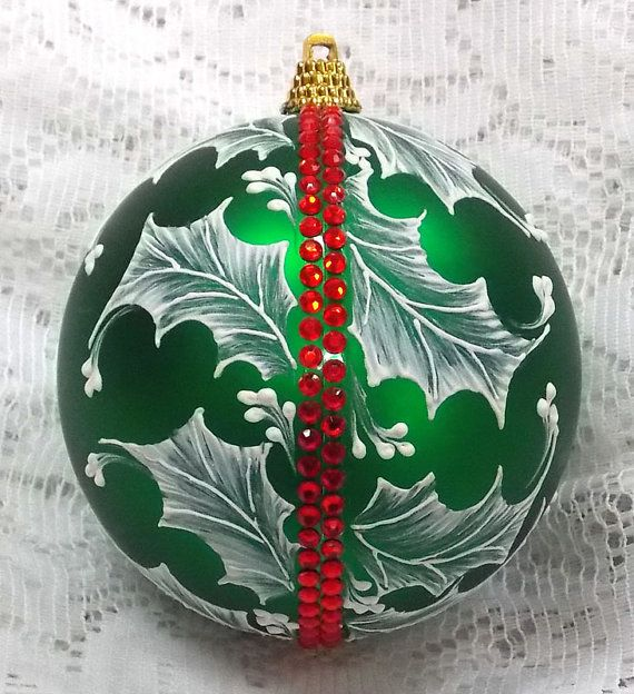 This rich green ornament is over-sized with a flowing design of hand painted white texture Holly and added red rhinestone trim. It would look