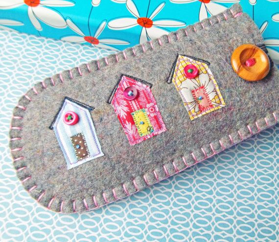 100% wool felt phone case with appliqued and hand embroidered beach huts design on the front. The case is fully lined with patterned cotton and has a