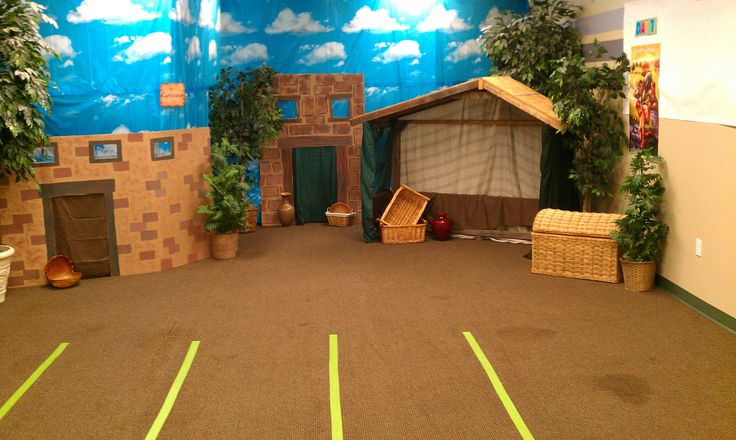 """Bible town set. We used the """"stable"""" from our Christmas Nativity scene as the main house. All other houses were sheets of cardboard. Background is Oriental Trading's """"Sky"""" backdrop. Plants were borrowed from other areas of the church building."""