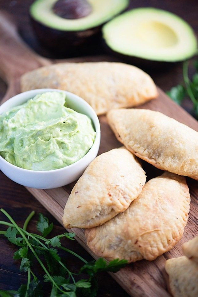 Save this recipe to make Carnitas Empanadas With Avocado Crema.