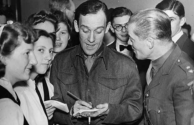 World War 2:  Uniformed comedian Tommy Trinder (1909 - 1989) giving his autograph at a Home Guard celebration.  April 21, 1943.