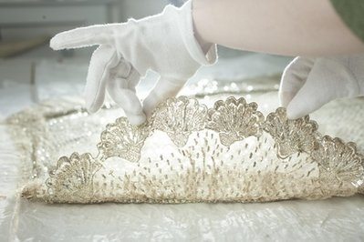 a conservator holds Princess Charlotte's elaborate cloth-of-silver empire line wedding dress embroidered with flowers and trimmed with Brussels lace.