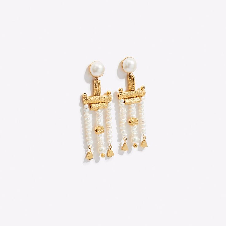 Inspired by new wave music and long nights on the dance floor, Lucy Folk's Talking Head's Earrings play with texture and tone. Contrasting miniature fresh water pearls with two larger Marbay pearls against a series of textured and high shine rods, these handmade earrings, available in yellow gold plated metal, make a bold statement with a masculine twist.