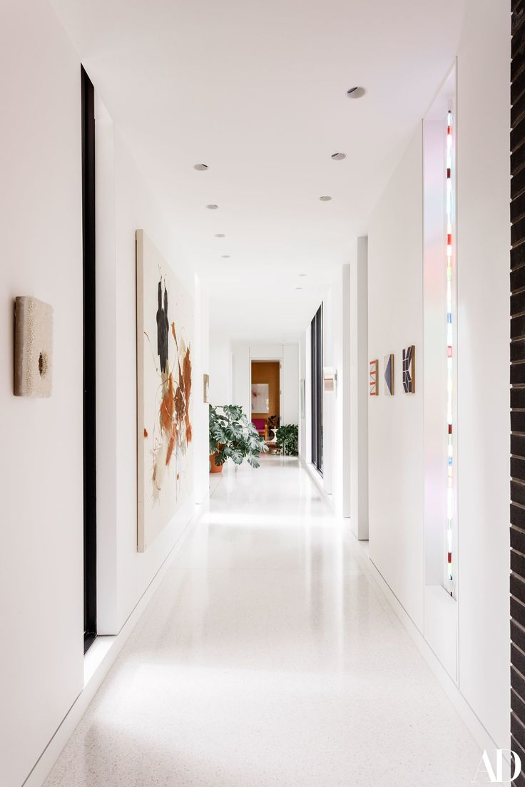 The stark white hallway showcases pieces from the Coles's modern art collection, including a large-scale painting by Elizabeth Neel. The white terrazzo floor tiles, seen throughout the home, are custom-designed by José Noé Suro of Suro Ceramics in Guadalajara, Mexico.