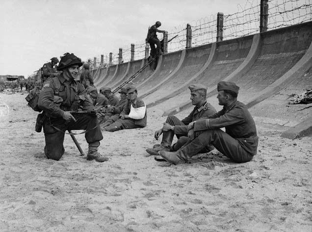 Corporal Victor Deblois of Le Régiment de la Chaudière guarding German prisoners on Juno Beach, Bernières-sur-Mer, France, 6 June 1944. Photographer: Frank L. Dubervill