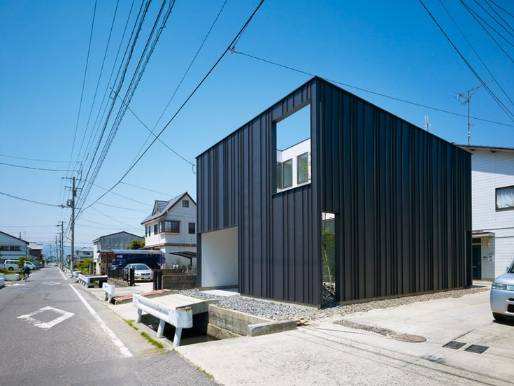 House In Imabari. By Hayato Komatsu Architects. Metal clad cube with window-like openings into internal courtyard spaces.