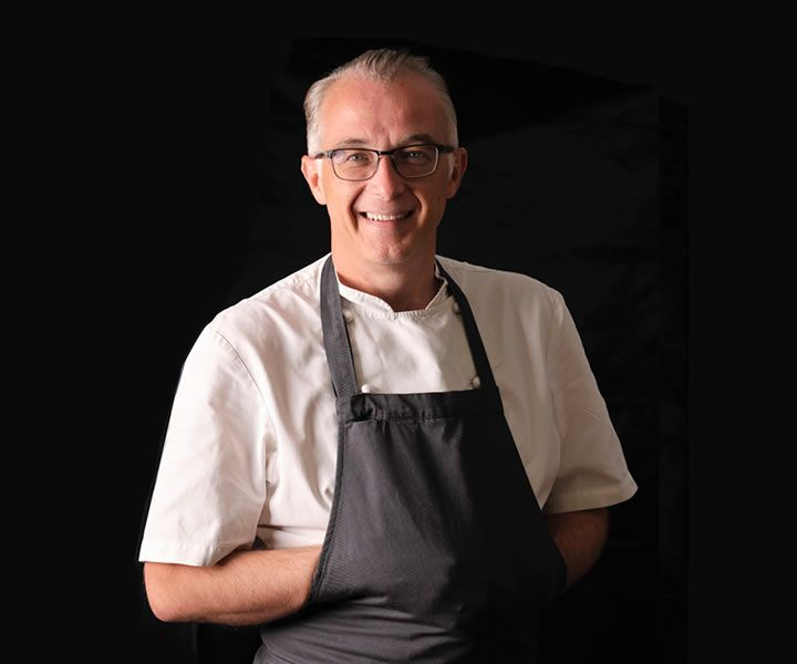 John knew from an early age that he wanted to be a chef and spent his early career working in some of Europe's best kitchens. In 1998 he achieved his first Michelin star in his first year at Lords of the Manor in Gloucestershire. In 2002 he moved to The Vineyard and in 2007 achieved two Michelin stars.