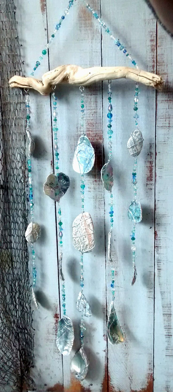This mobile is made with wire wrapped rough cut Abalone pieces, and strung with assorted blown glass and crystal beads, with a natural driftwood bridge. This ar