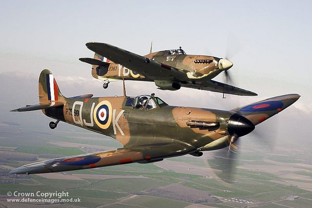 Spitfire P7350 (front) flies alongside Hurricane LF363 (back). The aircraft are part of the famous Battle of Britain Memorial Flight (BBMF) of historic RAF aircraft from the Second World War.