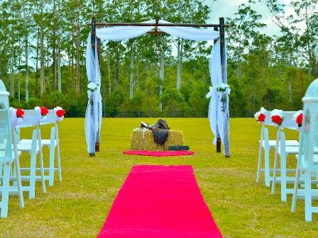Eternal Weddings Décor and Photography. Wedding Ceremony. Country Wedding Theme. Red Carpet Aisle Runner. Hay Bale. Horse Saddle. Lucky Shoe Horses. White Americana Chairs. Wedding Arbour. Wedding Chairs with flower decorations