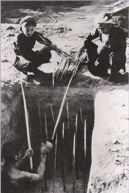 Viet Cong guerrillas laying punji trap near Cu Chi.