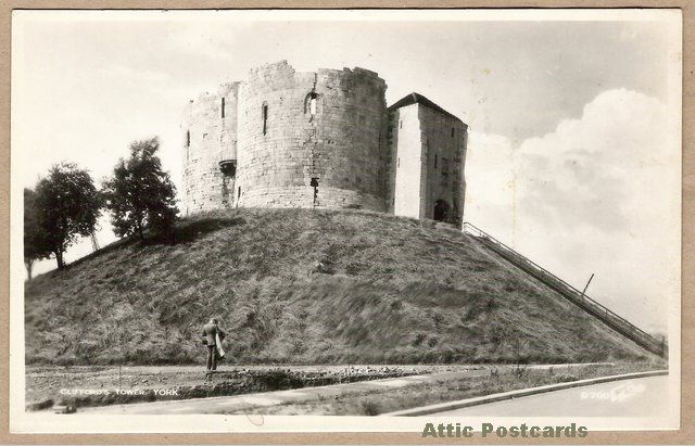 Vintage real photo postcard of Clifford's Tower in the City of York, Yorkshire, England. Depicts the tower and a man possibly photographing it.