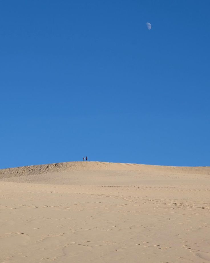 This photo was taken from the bottom of the Dune du Pilat looking upward some 100 meters to where those two people are standing at the summit. It felt like walking on another planet especially underneath the rising moon