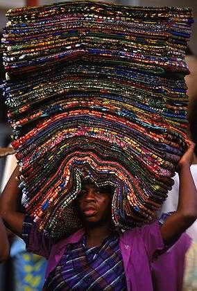A street vendor carrying/balancing wax-printed cotton cloth on her head. Lomé, Togo | © Cary Wolinsky.