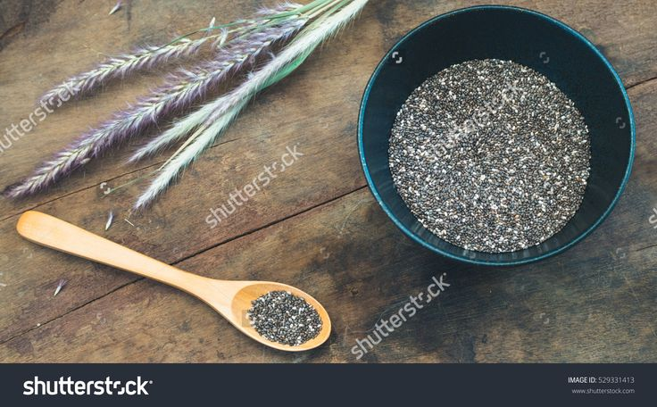 Chia seed in black bowl on wooden table - split toning effect