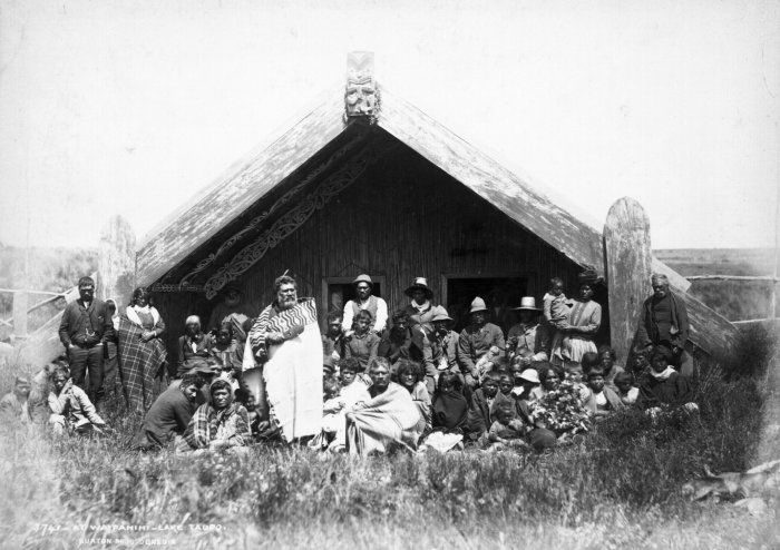 Maori group outside a meeting house at Waipahihi. Includes Te Rangi Tahau (standing), and Kiriwera (to his right). Photograph taken by the Burton Brothers probably between 1868 and 1898.