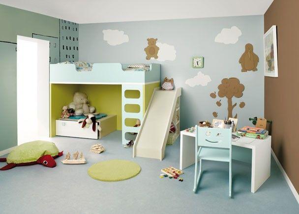 Habitación infantil con litera castillo con tobogán, escritorio y contenedor.