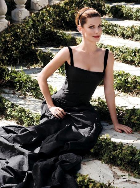 Sandra Bullock seated outdoors in a black evening dress...