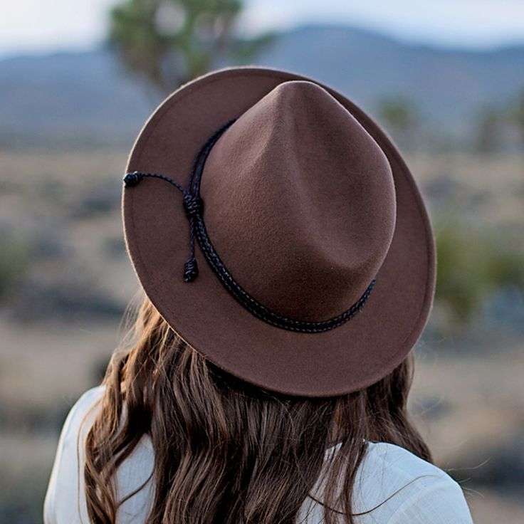 Accessorize your outfit with this wide-brim brown hat. This hat is made up of wool material and has a pinched crown. The brim on this hat is structured, not floppy. It also features a layered braided