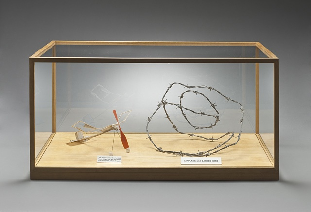 Chris Burden (United States, Massachusetts, Boston, born 1946)   Airplane and Barbed Wire, 1979  Mixed media installation, Model airplane, barbed wire, printed text, wood and glass case, Contemporary Art Deaccession Fund (M.2009.110a-e): Wood