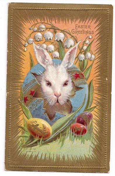 1912 Easter postcard showing a big white rabbit cracking through a big blue Easter egg