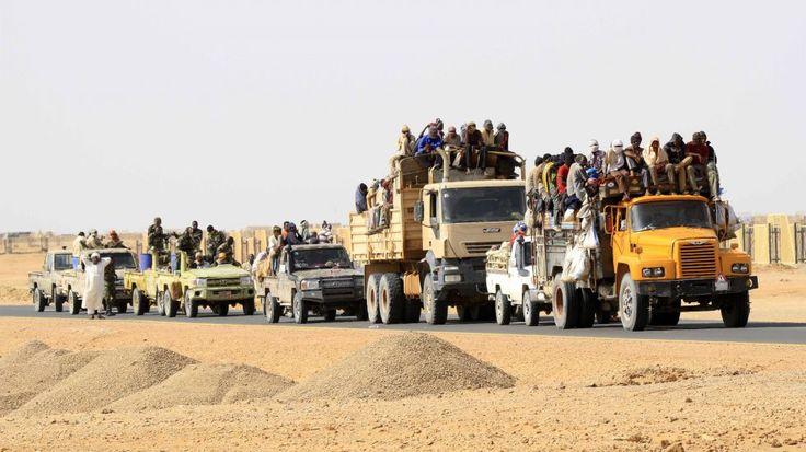 Lastwagen transportieren Flüchtlinge durch eine afrikanische Wüste