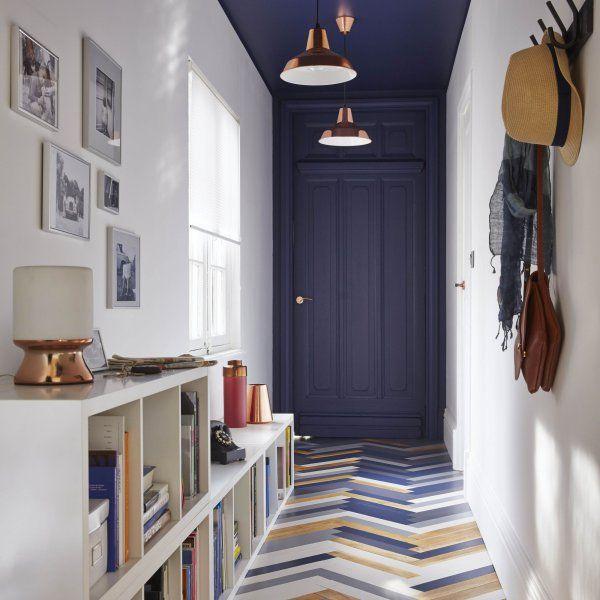 Dans cette entrée élégante, on a peint le plafond de la même couleur que la porte d'entrée pour mettre le couloir en valeur. On retrouve du bleu marine sur certaines lattes de parquet.