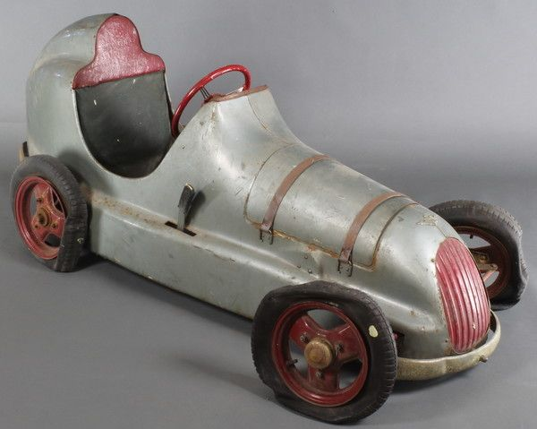 "Lot 250, A good late 1940's Austin Pathfinder pressed steel pedal car, complete with detachable bonnet revealing a faux engine and 4 dummy spark plugs 63"" long 22"" wide to outer wheel, 23 1/2"" high, set  £500 - 800"