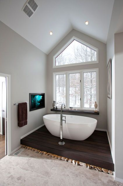 By Ryan Duebber Architect, LLC. Vaulted ceiling and large window achieve a feeling of spaciousness, enhanced by a minimalist approach and thoughtful layout. Freestanding bathtub sits on a platform made of Brazilian massaranduba wood, elevated to take advantage of the view.