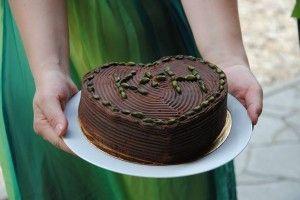 Dort můžete upéct i v srdcové formě. Na obrázku je bezlepkový dort s čokoládovým krémem a pistáciemi.