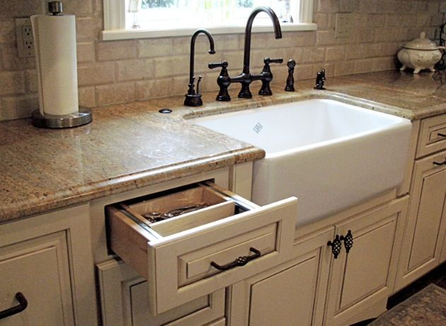 White farmhouse sink, quartz counter tops, Irish cream cabinets with oil rubbed bronze fixtures