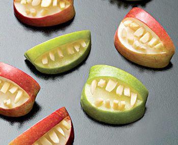 Разрезаем яблоко на четыре части, удаляем сердцевину и делаем ножом разрез в виде открытого рта. Вместо зубов вставляем очищенный миндальный нарезанный орех.