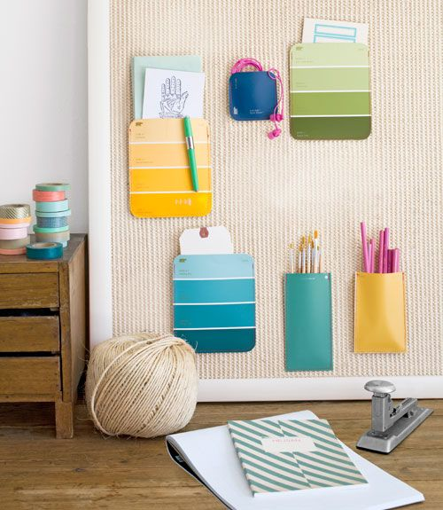 "Repurpose hardware-store color cards in seconds flat: Simply stack two same-size cards atop each other, right sides facing out, and stitch together along the bottoms and sides with contrasting thread (we opted for red). Then use flathead tacks to attach your brilliant little pocket organizers to a bulletin board, and fill them with pencils, papers, and more. (Sisal bulletin board, $149; 24""W x 36""H; ballarddesigns.com)   - CountryLiving.com"