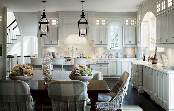 Alexa Hampton - Lovely kitchen with floor to ceiling white kitchen cabinets, white, kitchen island, marble countertops, farmhouse sink, marble tiles backsplash, iron lanterns, wood dining table, settee and wicker chairs.