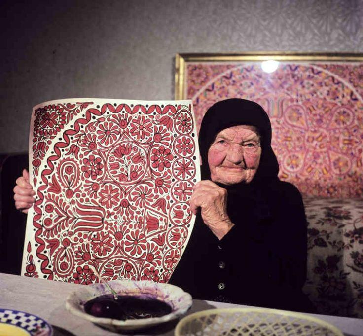 Katarína Brinzová pri predkresľovaní vzorov nástennej maľby. Veľký Grob (okr. Galanta), 1973. Archív diapozitívov Ústavu etnológie SAV.  Foto A. Pranda