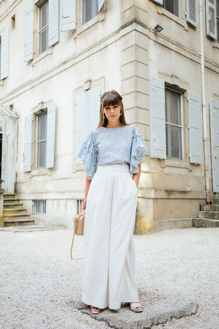 White high-waisted trousers and the cutest baby blue top with a beautiful French castle as the backdrop.