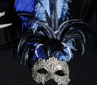 Maschera decorata con piume di color nero, blu scuro e blu chiaro. Maschera originale veneziana realizzata a mano in cartapesta. Decorata con foglia d'argento, tecnica dello screpolato, pizzo macramè ed impreziosita da cristalli Swarovski e perle.