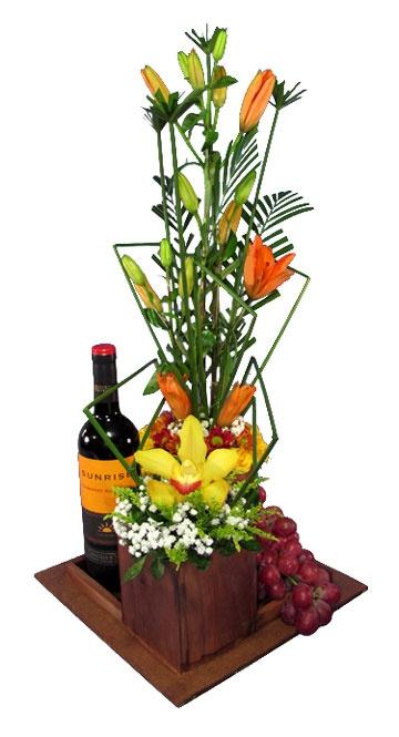 Hermoso y original arreglo en base de madera con delicada orquídea, acompañado de racimo de uvas y vino.
