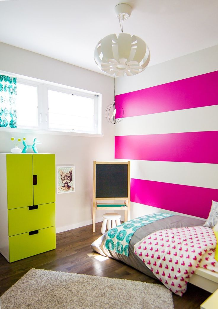 Striking fuchsia (bordering on neon) pink accent wall in this girl's modern bedroom.
