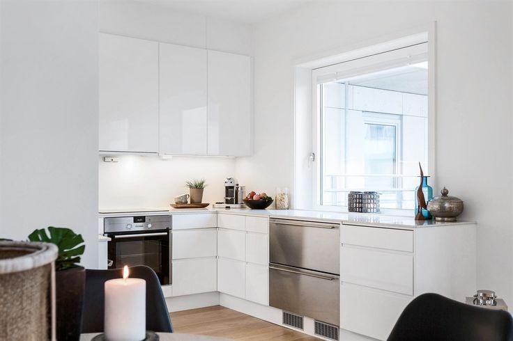 Kjøkken med hvite høyglans fronter, granitt benkeplate med underlimt oppvaskkum, kjøkkenventilator, integrert komfyr med induksjonstopp | Drømmekjøkkenet