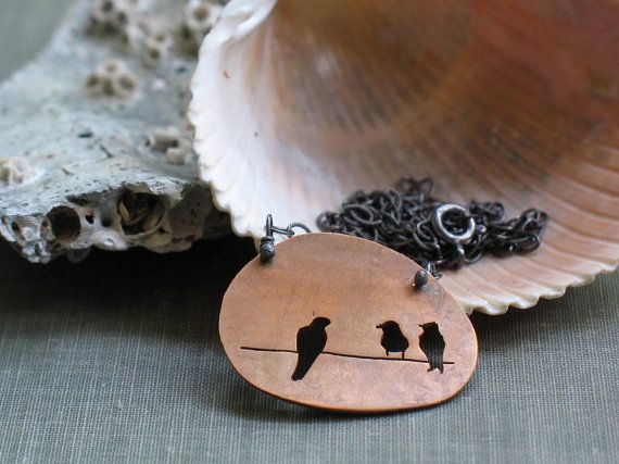 a trio of birds sit on a wire. hand pierced with a jewelers saw into a copper penny that was smashed on the train tracks.