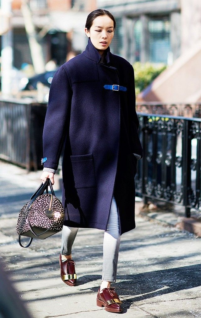 Fei Fei Sun wears a long coat with buckle detailing, skinny jeans, oxfords, and an animal print satchel